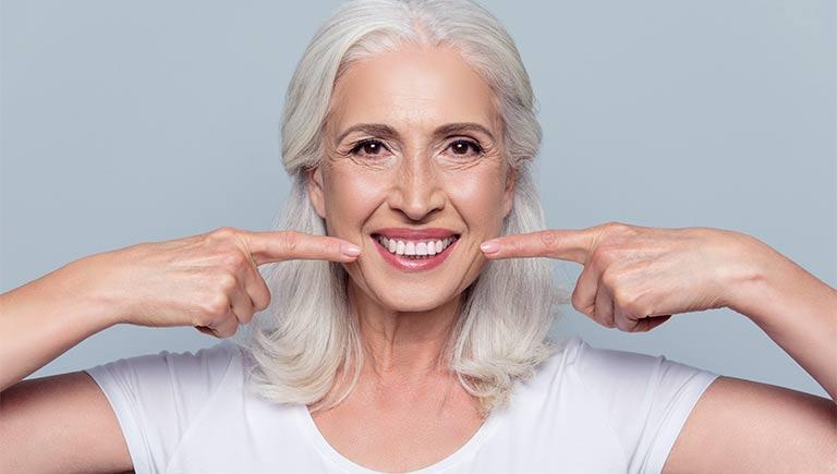 Frau zeigt ihr lächeln nach Parodontose Behandlung